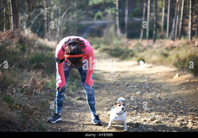 A woman rests after running up a steep hill with her small dog - Stock Image
