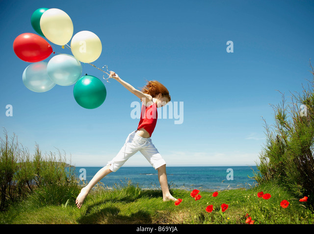 Young girl running with balloons - Stock Image