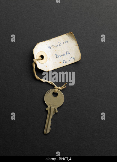 Old key with label with the witing 'Studio Door B-9' - Stock-Bilder