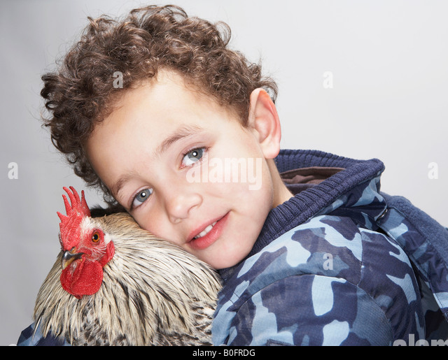 Close up of boy and cockerel - Stock Image