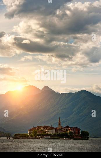 Sun shining over castle built on island - Stock Image