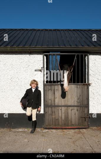 Boy standing by horse stables - Stock-Bilder