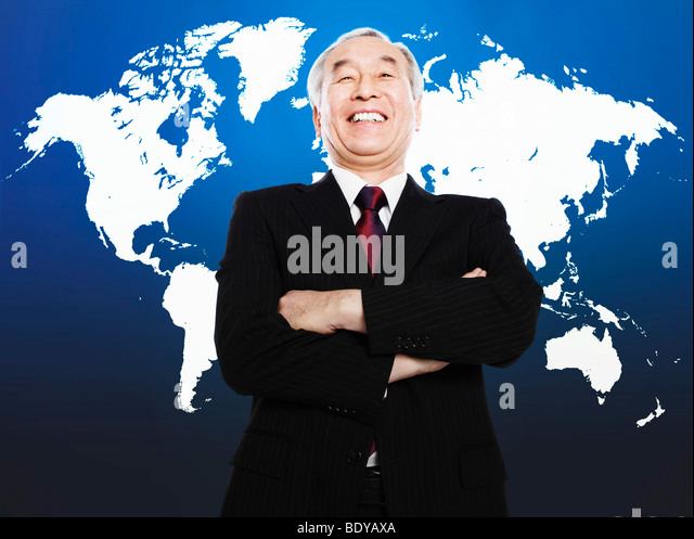 Asian man smiling in front of world map - Stock Image