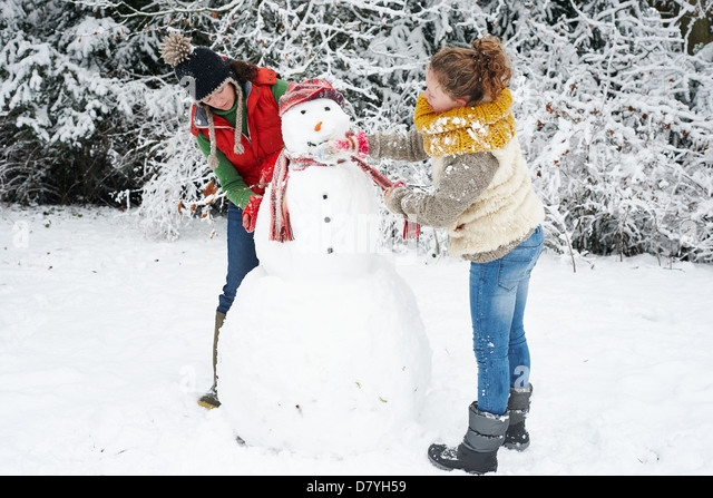 Mother and daughter making snowman - Stock Image