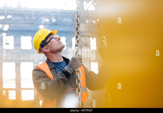 Steel worker holding chain in factory - Stock Image