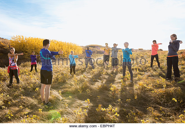 Group fitness stretching in sunny rural field - Stock Image