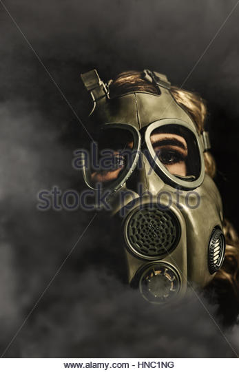 Young woman in a gas mask - Stock Image
