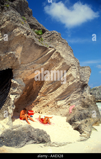 Bermuda Landmark Geology pink beach couple relaxing on beach under rock formation - Stock Image
