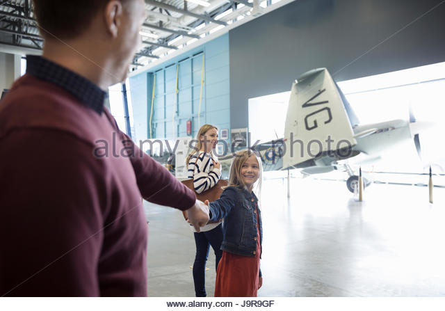 Family holding hands, walking toward propellor airplane in war museum hangar - Stock-Bilder