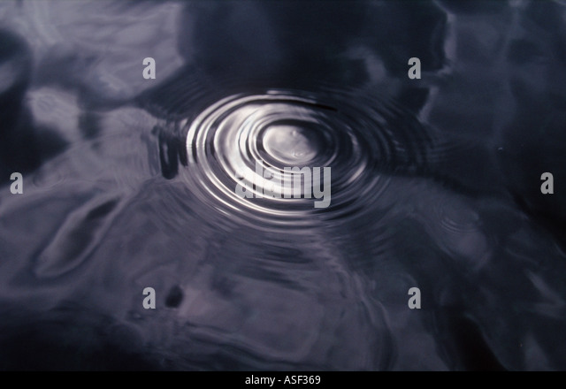 Spreading ripples from water dropping onto sea surface reflecting sunlight in cloudy sky - Stock Image