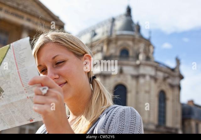 France, Ile-De-France, Paris, Versailles, Teenage girl  reading map at Chateau De Versailles - Stock Image