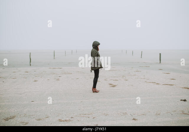 Woman standing on the empty beach - Stock Image