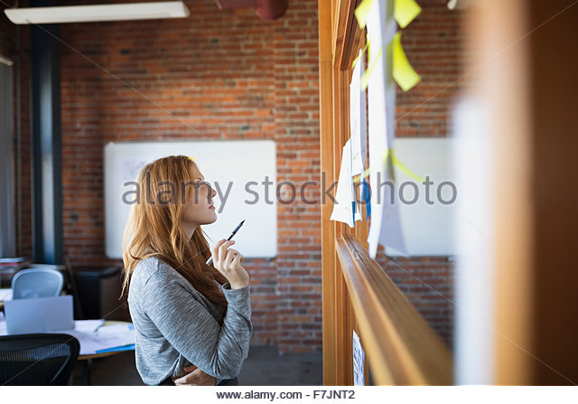 Businesswoman brainstorming looking up at paperwork in office - Stock Image
