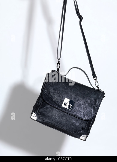 Black leather handbag on white background - Stock Image