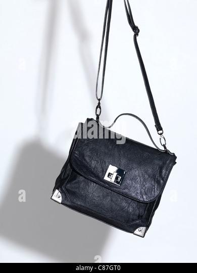 Black leather handbag on white background - Stock Image