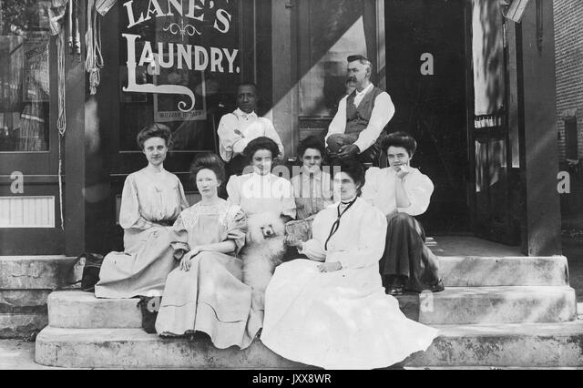 A group of six young women and two young men, all with neutral expressions, sit with a dog on the steps to a storefront - Stock Image