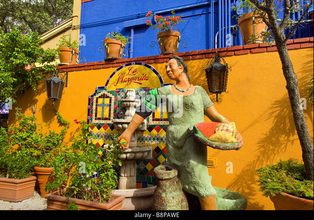 Market Square San Antonio Texas tx with colorful statue of a Mexican woman beside water fountain and bright yellow - Stock Image