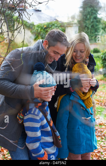 Parents covering children's eyes outdoors - Stock Image