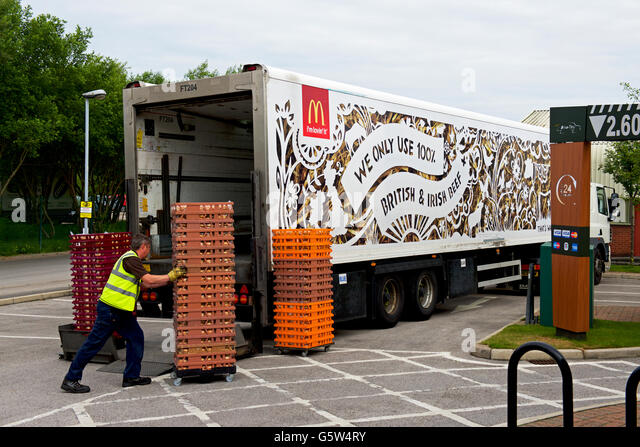 Man delivering to a branch of McDonalds, England UK - Stock Image