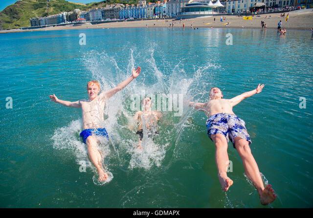 Aberystwyth, Wales, UK. 19th July, 2016. UK weather: Three teenage boys enjoying themselves jumping off the jetty - Stock Image
