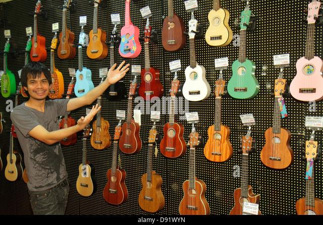 Thailand Bangkok Chatuchak Phaholyothin Road Music Hut musical instruments sale store Asian man ukuleles - Stock Image