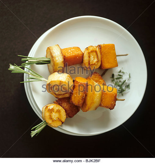 Baked sweet potato and parsnip on rosemary skewers - Stock Image