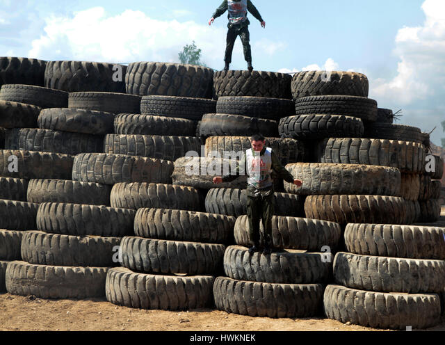 Athletes overcome a bunch of tires. - Stock Image