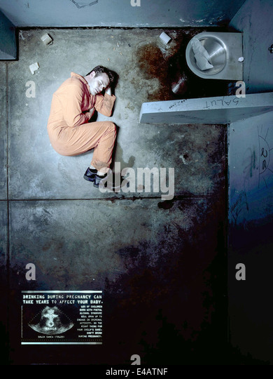 SANCA (South Africa, 2010) fetal alcohol syndrome awareness campaign poster. Criminal in fetal position. See description - Stock Image