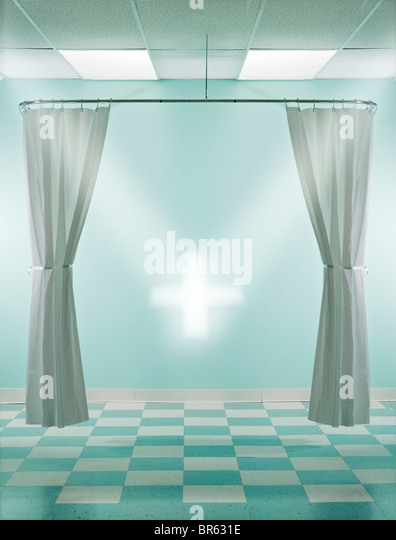 green and white hospital room with cross of light - Stock Image