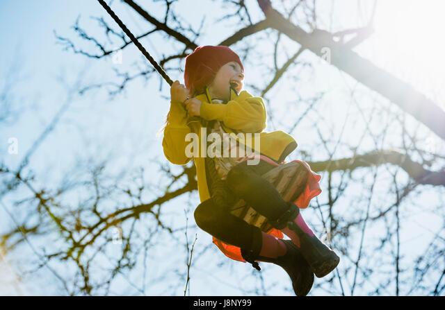 Girl (4-5) swinging on rope - Stock-Bilder