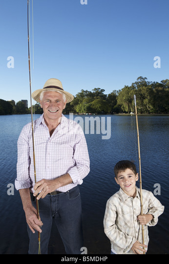 An elderly man fishing with boy - Stock Image