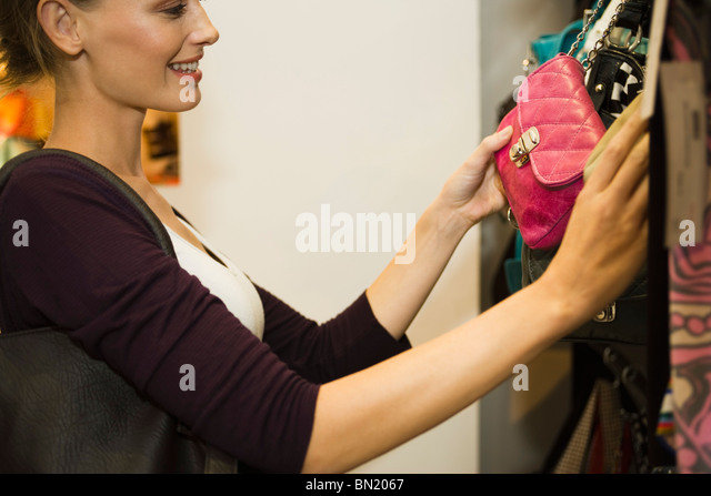 Woman looking at purse in shop - Stock Image