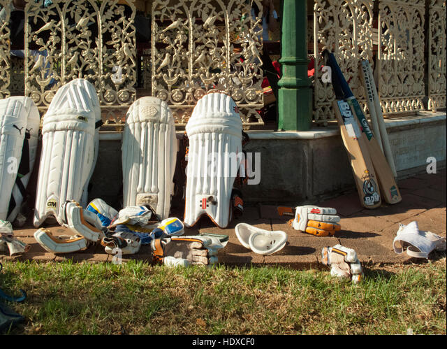 Cricket gloves bat and pads leaning up against decorative iron fence in afternoon light - Stock-Bilder