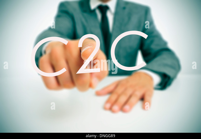 man wearing a suit sitting in a table pointing to the word C2C, consumer-to-consumer, written in the foreground - Stock Image