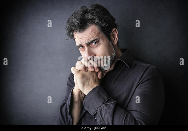 Worried man praying inside - Stock Image