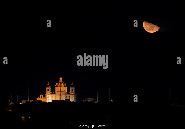 Rising moon above the parish church of Zejtun, Malta, Europe - Stock Image