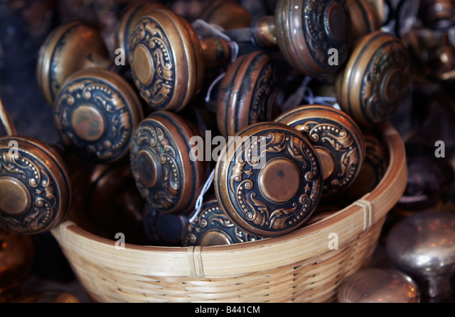 A wicker basket of brass doorknobs on display in an architectural antiques store - Stock-Bilder