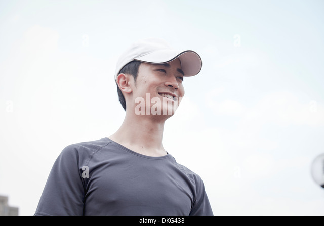 Male jogger wearing baseball cap, looking away - Stock Image