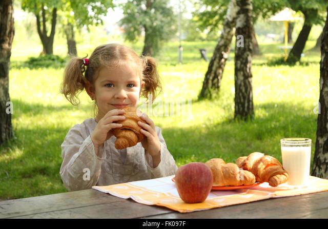 young girl eat croissant - Stock-Bilder