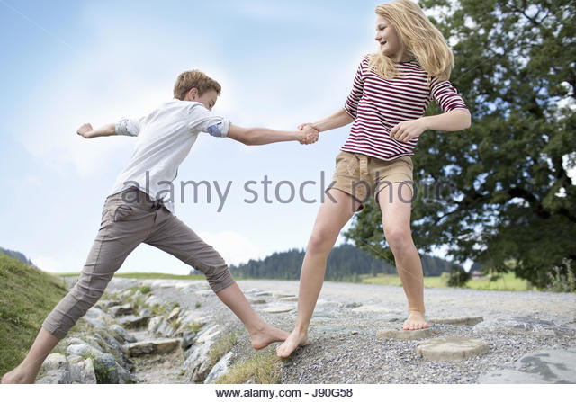 Teenager Boy And Girl Helping Each Other To Cross Stream - Stock-Bilder