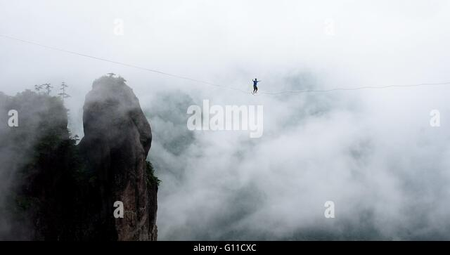 Taizhou, China's Zhejiang Province. 7th May, 2016. A slackline walker takes his chance up in air during a slackline - Stock Image