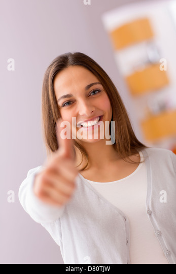 bright picture of young woman with thumbs up - Stock Image