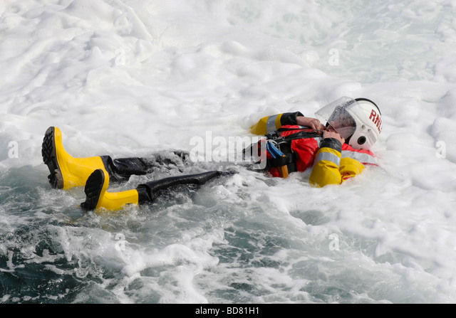 An RNLI crewman practising man over board drills - Stock Image