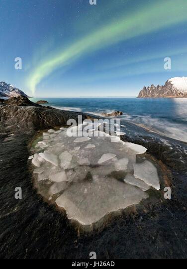 The Northern Lights illuminate the rocky peaks and icy sea in the polar night, Tungeneset, Senja Troms, Norway - Stock Image