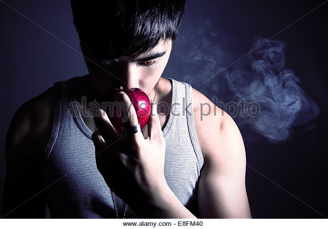 Portrait of a man holding an apple - Stock Image