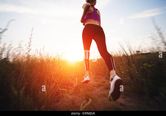 Young woman running on a rural road at sunset in summer field. Lifestyle sports background - Stock Image