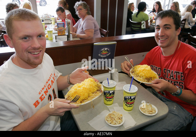 Ohio Cincinnati Skyline Chili Restaurant smiling men table cheese plate food - Stock Image