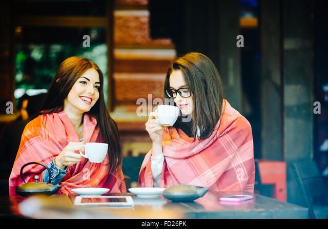 Two young and beautiful girls gossiping - Stock Image