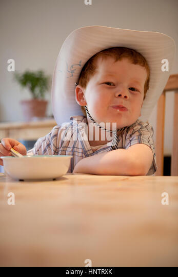 A five year old boy eating his cereal at breakfast. - Stock Image