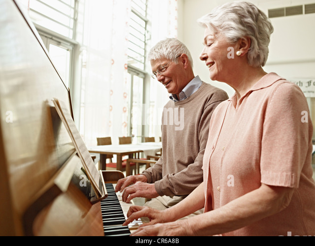Germany, Cologne, Senior couple playing piano in nursing home - Stock Image